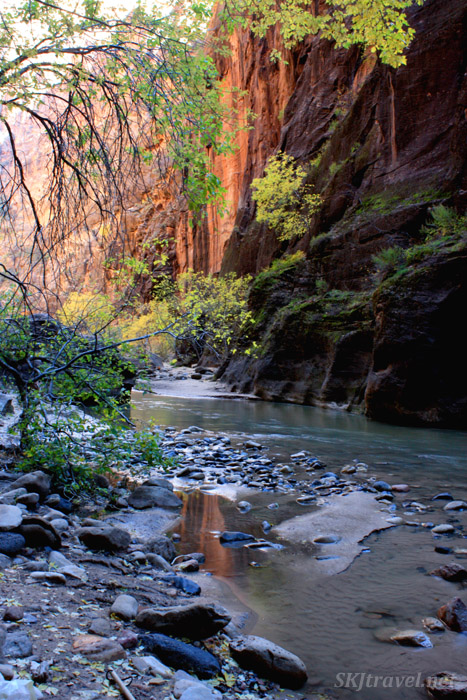 Shallow river in steep red canyon.