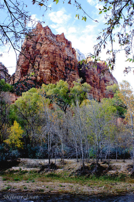 Tall red rock formation with trees in foreground. Zion.