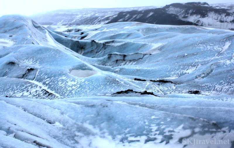 Glacier landscape, blue snow and ice, black volcanic rock and ash, Iceland.