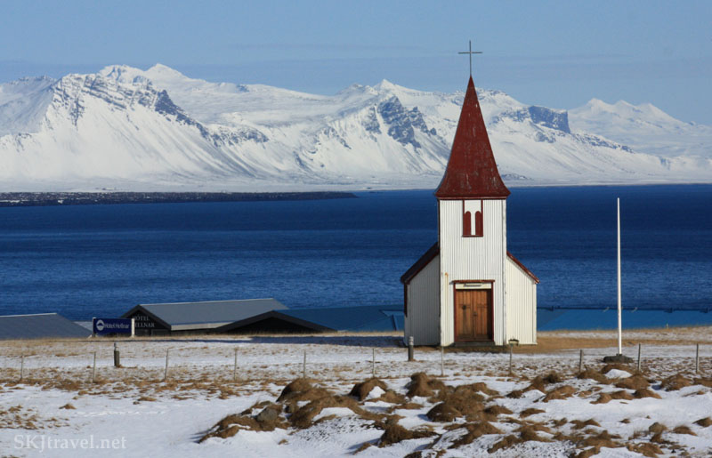 red roofed church next to ocean