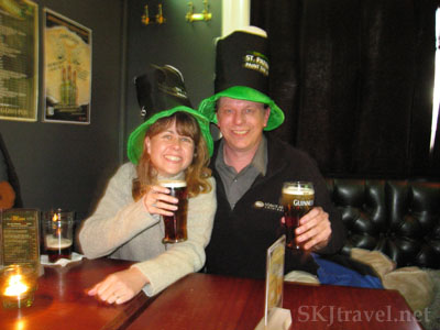 two people with tall top hats and beers