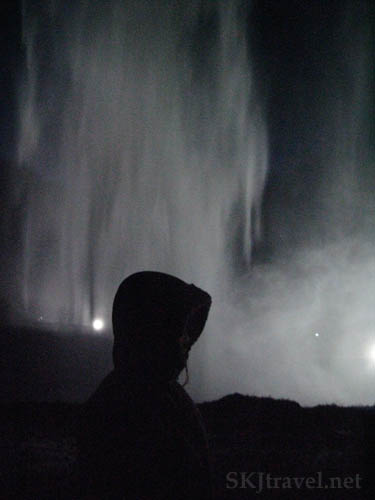 girl in front of waterfall at night