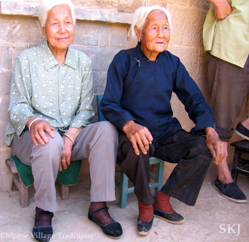 Two elderly women sitting in a courtyard in rural peasant village in Shaanxi Province, China, one woman with bound feet. Photo by Shara Johnson