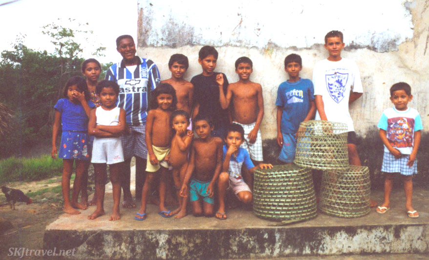 Children standing on a decaying cement building with fish baskets, Brazil.