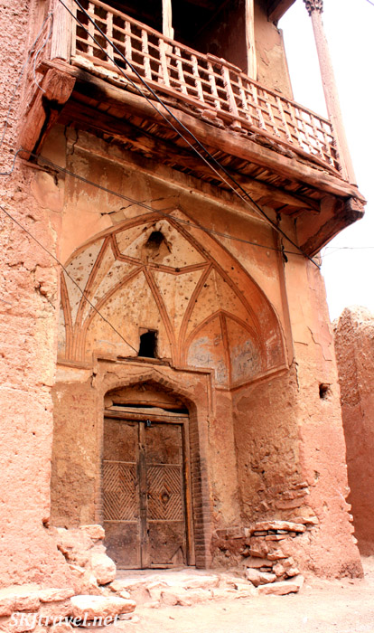 Door with decorative fresco above and a balcony above it, now in decay. Red Village, Iran.