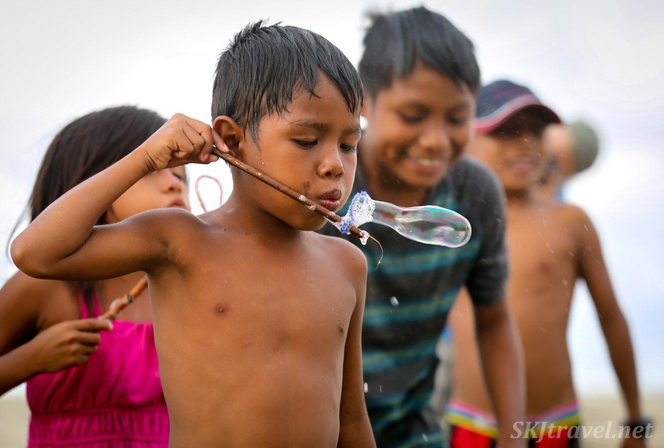 Child blowing bubbles with homemade bubble wand, turtle festival in Guna Yala village of Armila. May 2019