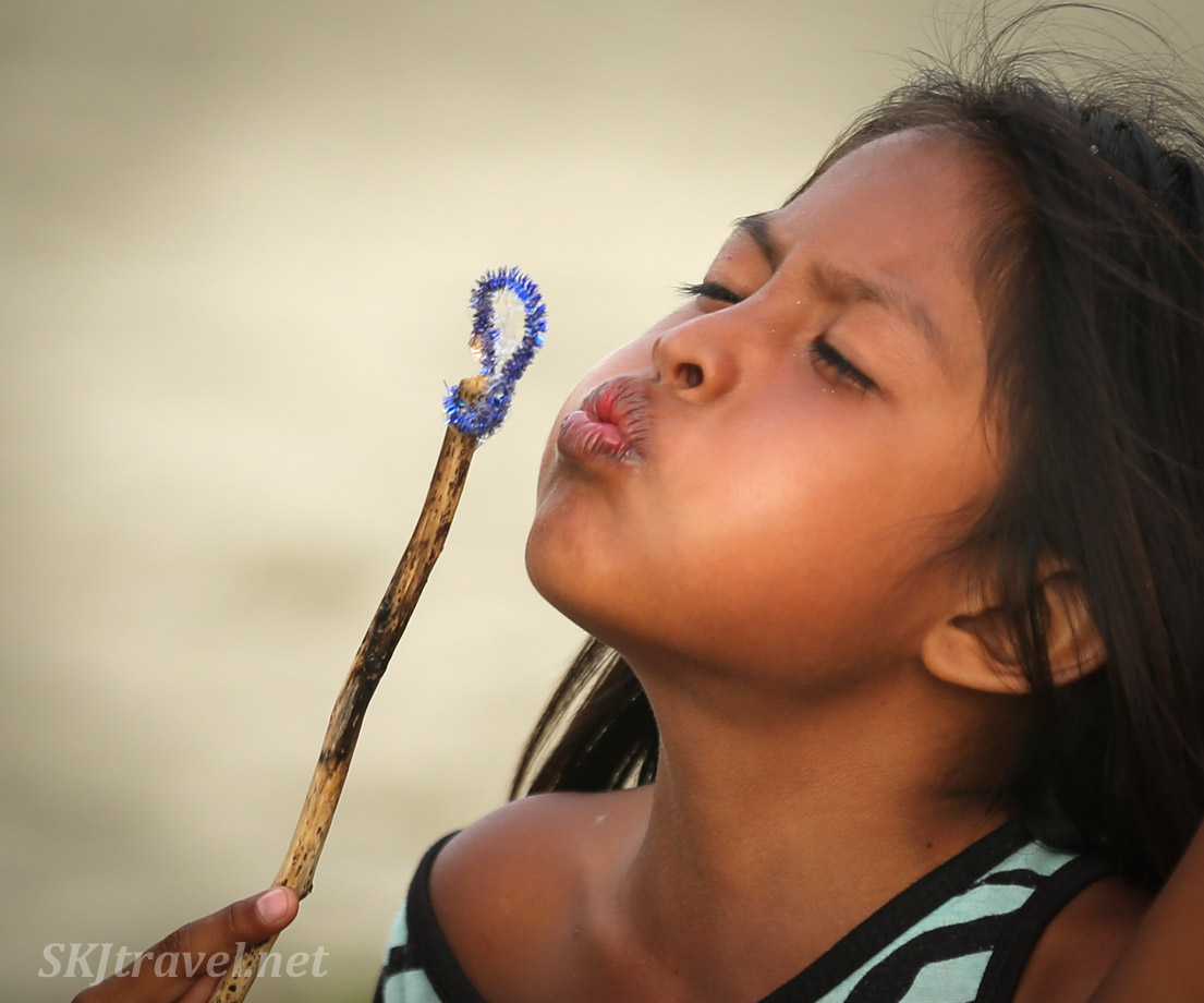 Child blowing bubble with a homemade bubble wand at the turtle festival in Guna Yala village of Armila, Panama. May 2019.