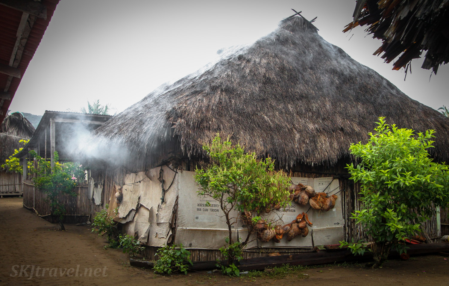 Street corner in Armila village, Guna Yala, Panama. Large hut with smoke seeping out of the thatched roof.