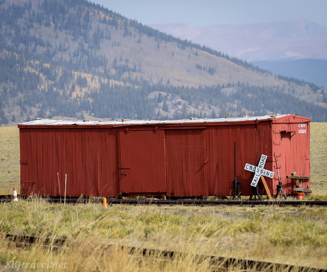 Old red rail car sitting in a meadow near the stone roundhouse of the South Park narrow gauge line at Como, Colorado.