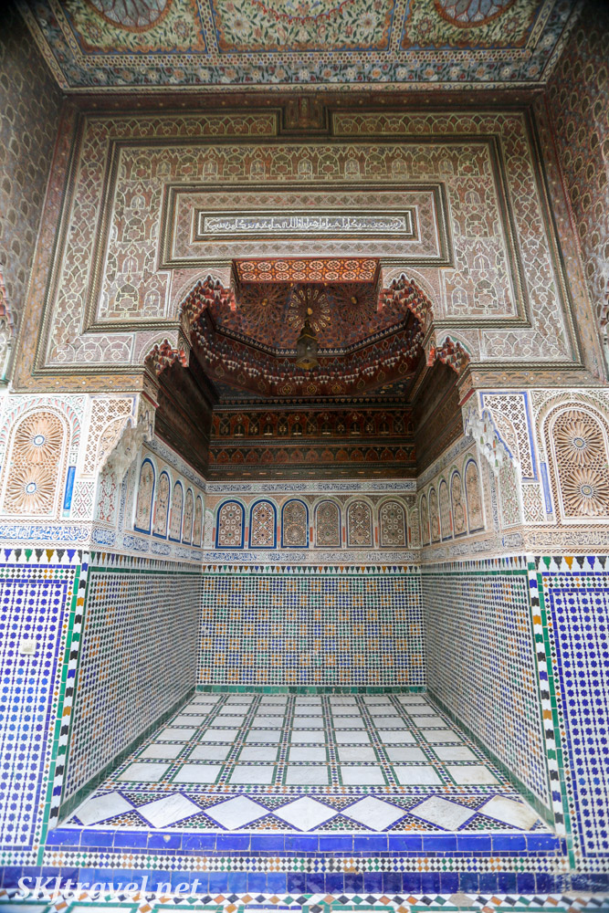 Very ornate nook Bahia Palace, Marrakech, Morocco. Moroccan carved stucco, painted cedarwood ceiling, colorful tilework. UNESCO World Heritage.