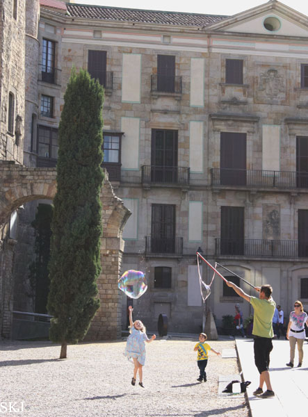 Two children jump up trying to catch a giant bubble in Barcelona. Photo by Shara Johnson