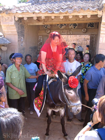 Woman dressed in red on a donkey with a red bow and villagers gathered round for a wedding procession, Shaanxi Province, China. Photo by Shara Johnson