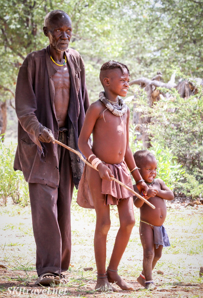 A Himba adolescent girl leads a blind man with a stick and holds hands with a toddler. Kunene region of Kaokoland, Namibia.
