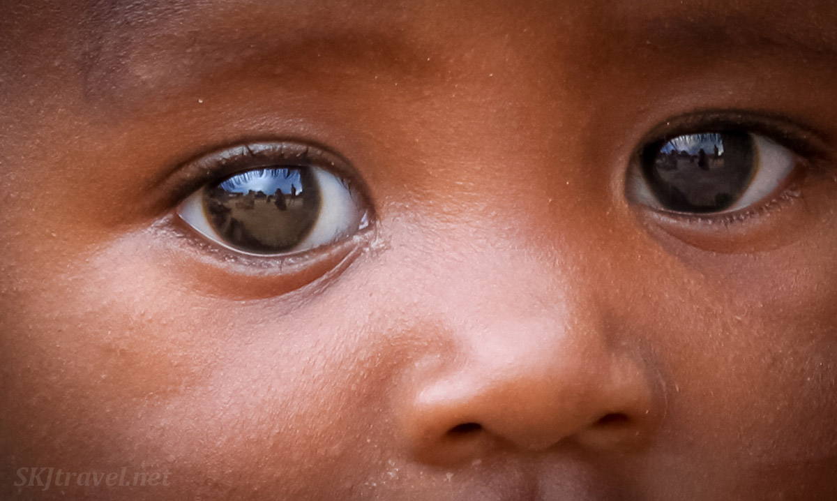 The film of The African Witchfinder and I reflected in a Himba toddler's eyes. Kaokoland, Namibia.