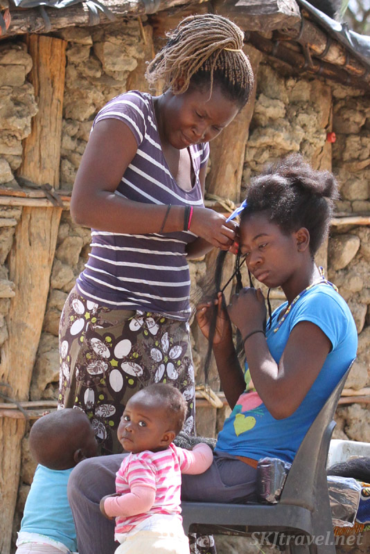 Woman braiding another woman's hair with hair extensions. Okahandja, Namibia.