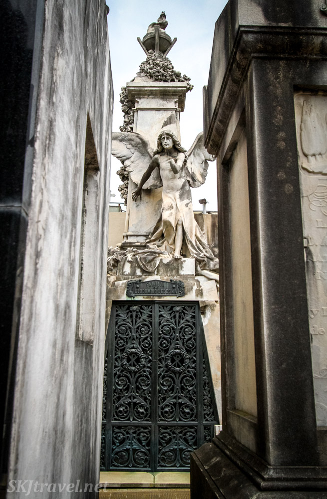 Stone statue of angel at the end of a corridor in Recoleta Cemetery, Buenos Aires, Argentina.