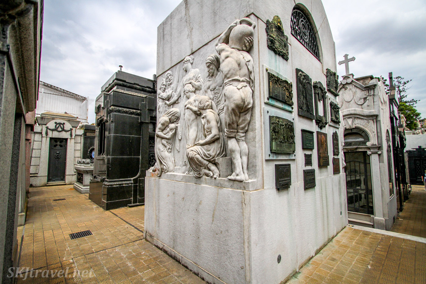 Multiple commemorative plaques on the outer walls of a mausoleum in Recoleta Cemetery, Buenos Aires, Argentina.