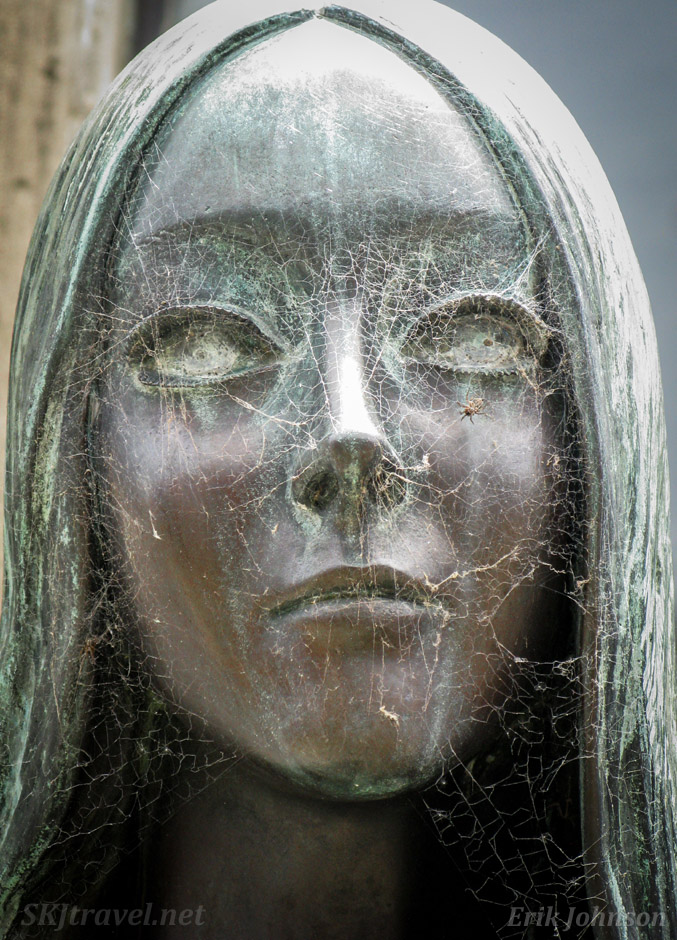 Cobwebs cover the face of the bronze sculpture at the tomb of Liliana Crociati de Szaszak at Recoleta Cemetery, Buenos Aires, Argentina.
