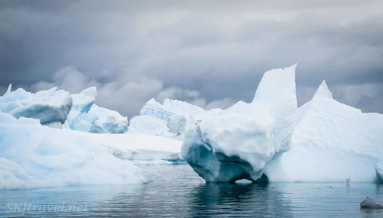 Huge dramatic icebergs seen from our kayak at Cuverville Island, Antarctica.