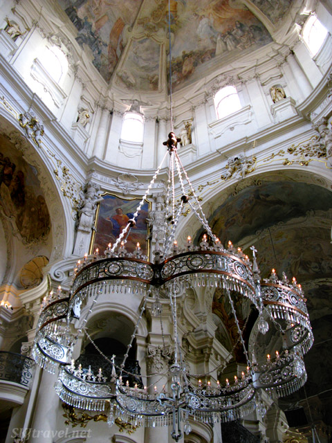 Interior of church on the outskirts of the Old Town Square, Prague, elaborately painting ceilings and huge glass chandalier.