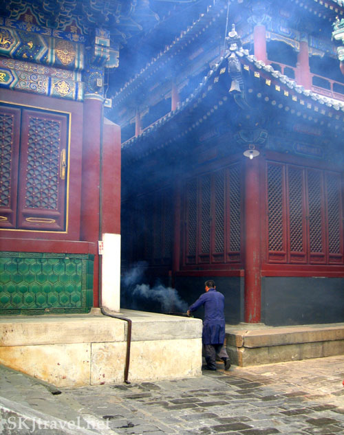 Monk carting away smoldering ashes from the fire boxes where people burn incense at the Lama Temple, Beijing, China.