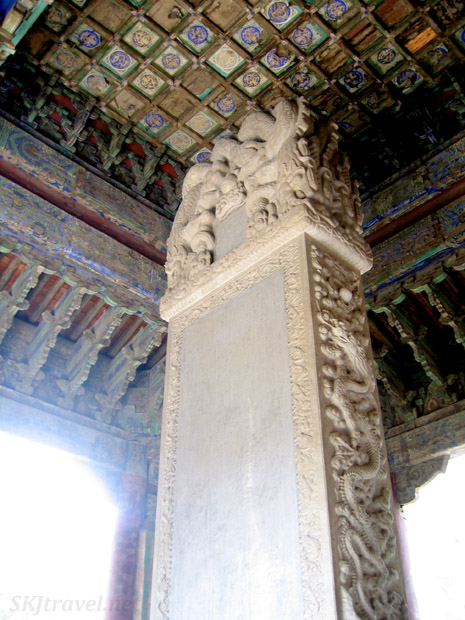 Dilapidated ceiling inside a building at the Confucian temple, an inscribed stone stele reaching up toward it. Beijing, China.