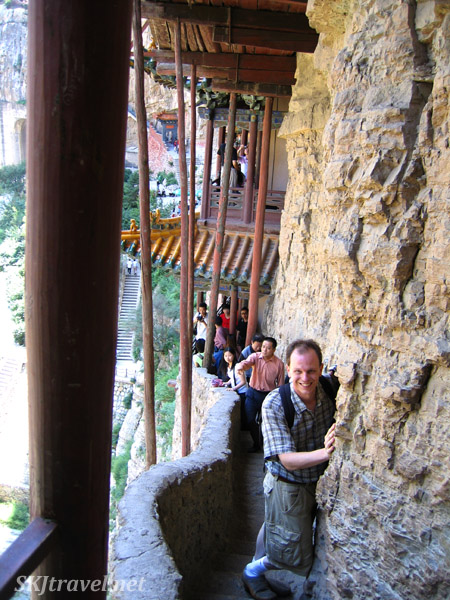 man walking a narrow walkway on a cliffside