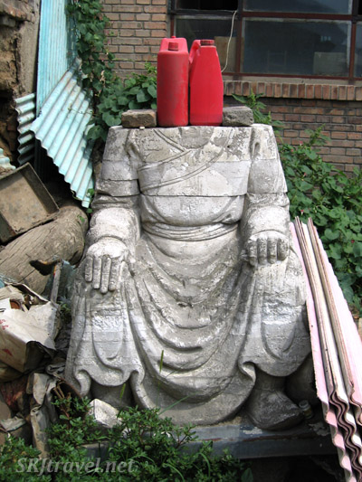 stone statue without head and gas cans sitting on top