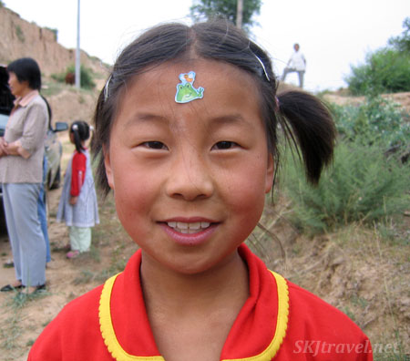 Little Xiu-Xiu and her frog sticker. Dang Jiashan village, Shaanxi Province, China.