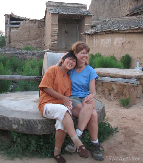 "My ""shadow,"" Wang-Wang, and I sitting on the grinding mill just beside the loo. Dang Jia Shan village, China."