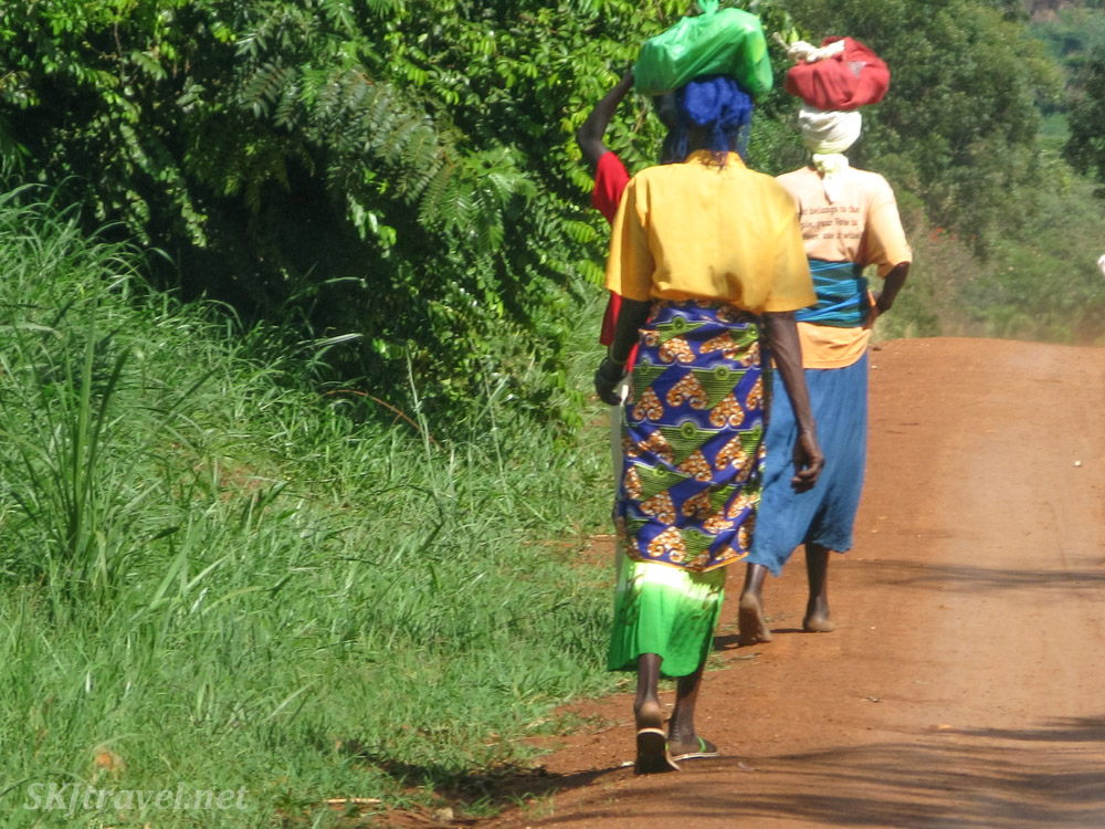 Women walking along the roadside in rural Uganda, carrying bags on their head.