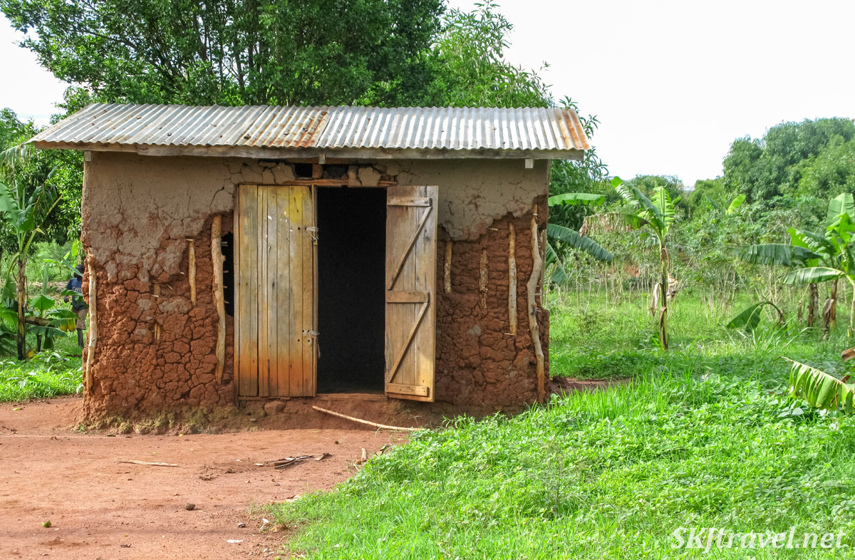 Mud shack with wooden doors along the roadside, rural Uganda.