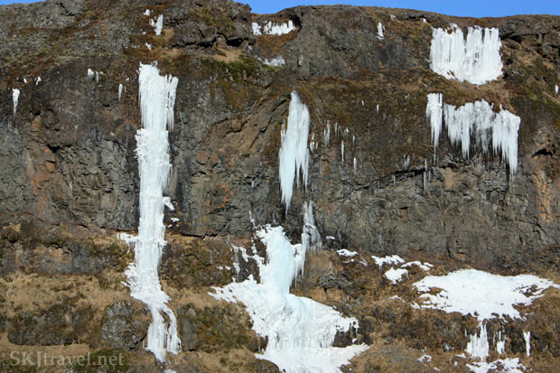 The trail to Glymur Falls, Iceland. Frozen water seeping from rock wall.