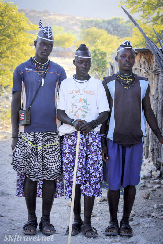 Three young Himba men walking through a modern village in Kaokoland, Namibia, illustrating traditional hairstyles and jewelry mixed with modern clothing.