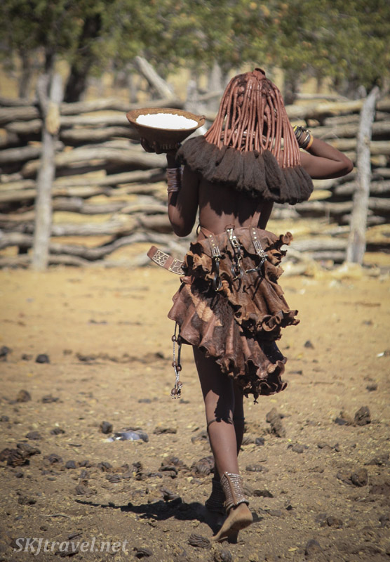 Young Himba woman carrying a basket of flour inside her kraal, Kaokoland, Namibia. You can see the detail of her cow hide skirt.