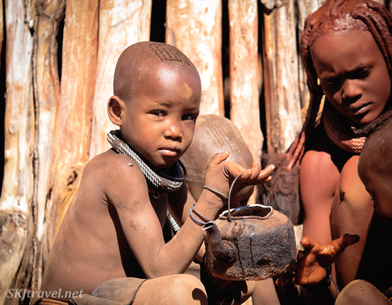 Himba child holds a rusted tea kettle of water for a mother washing her baby's face. Kaokoland, Namibia.