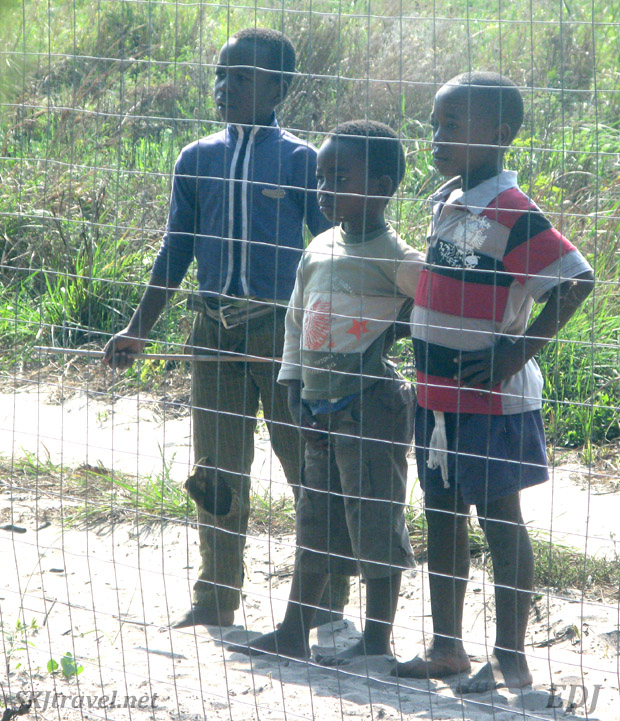 "Kids standing outside the fence of a tourist ""resort"" Sodwana Bay, South Africa."