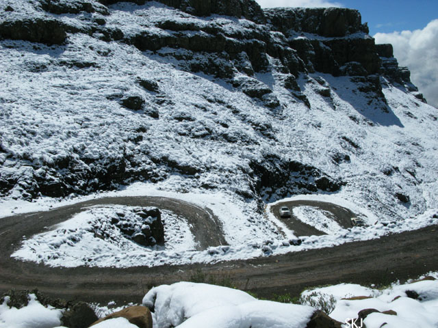 Two hairpins in a road with snow-covered roadside