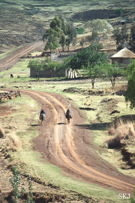 two men on horseback riding down dirt road in mountains