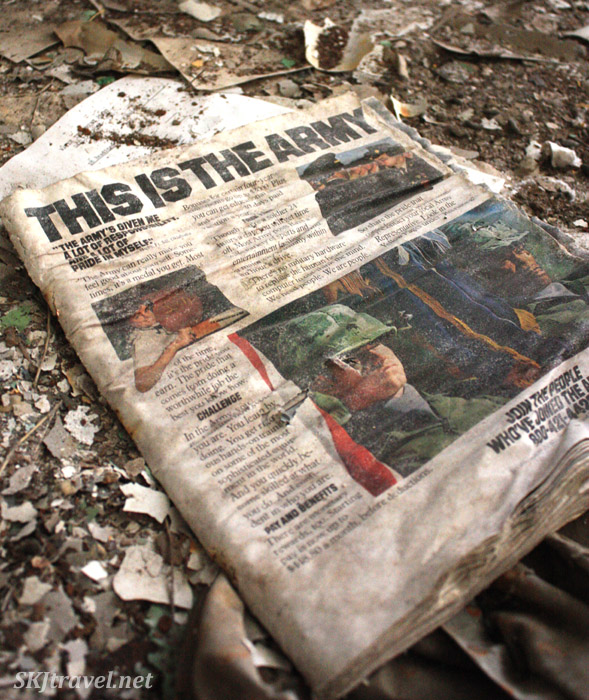 "Old newspaper with front page headline ""This is the Army"" on the floor in abandoned building in Gilman, Colorado."