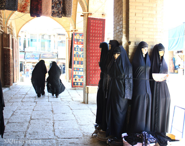 Mannequins wearing chadors and two women in chadors walking through an outdoor shopping area outside the Friday Mosque, Isfahan, Iran.