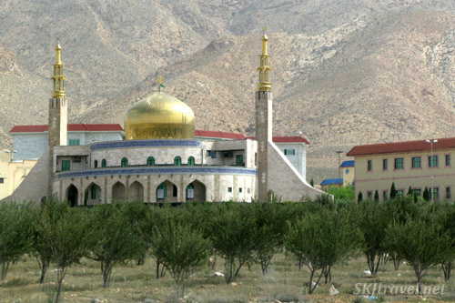 Typical town mosque, along the roadside in central Iran. Orchard in foreground.