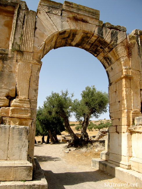 Large stone triumphal arch with trees on the other side in Dougga Tunisia. photo by Shara Johnson