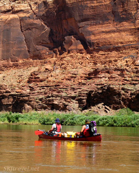 Padding 2 man canoes down the Green River, Utah. Reflection on the water.