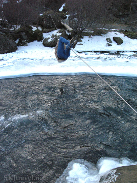 Shara crossing the swift icy river hanging by hands and legs from a cable wire, Glymur Falls, Iceland.